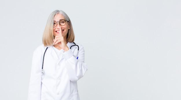 Middelbare leeftijd arts vrouw op zoek serieus en kruis met vinger tegen lippen gedrukt eist stilte of stil, geheimhoudend