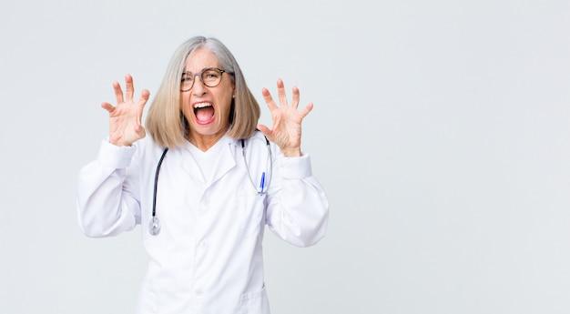 Middelbare leeftijd arts vrouw schreeuwen in paniek of woede, geschokt, doodsbang of woedend, met de handen naast het hoofd