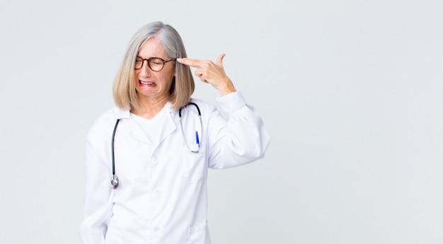 Middelbare leeftijd arts vrouw zoekt ongelukkig en gestrest, zelfmoord gebaar pistool teken met de hand maken, wijzend naar het hoofd
