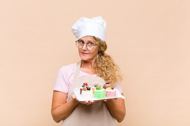 Middelbare leeftijd bakker vrouw koken taarten