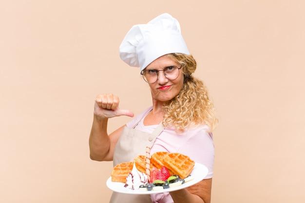 Middelbare leeftijd bakker vrouw koken wafels