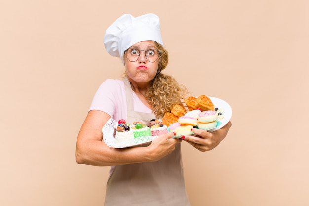 Middelbare leeftijd bakkersvrouw met cakes