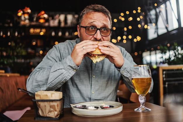 Middelbare leeftijd bebaarde hongerige man zit in restaurant en heerlijke hamburger eten.