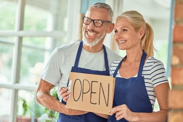Middelbare leeftijd blanke eigenaren van winkel met open bord