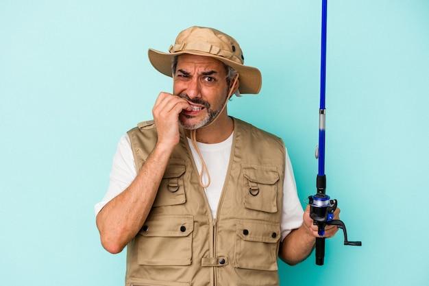 Middelbare leeftijd blanke visser met staaf geïsoleerd op blauwe achtergrond vingernagels bijten, nerveus en erg angstig.