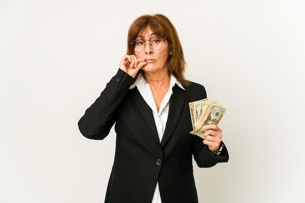 Middelbare leeftijd blanke zakenvrouw met bankbiljetten geïsoleerd met vingers op lippen die een geheim houden.
