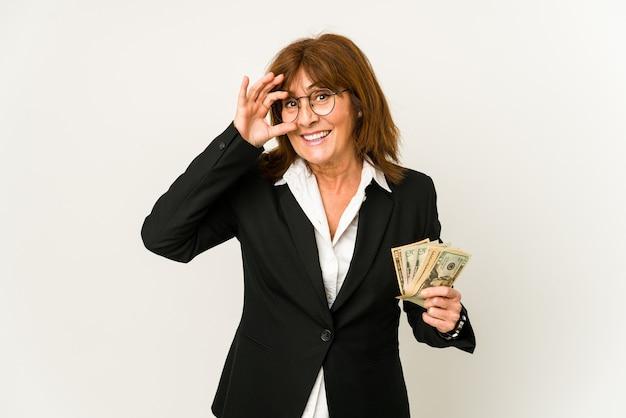 Middelbare leeftijd blanke zakenvrouw met bankbiljetten geïsoleerd opgewonden houden ok gebaar op oog.