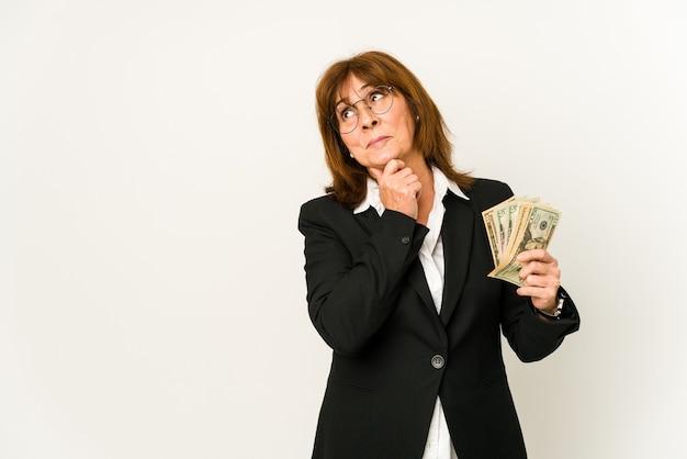 Middelbare leeftijd blanke zakenvrouw met bankbiljetten geïsoleerd zijwaarts kijken met twijfelachtige en sceptische uitdrukking.