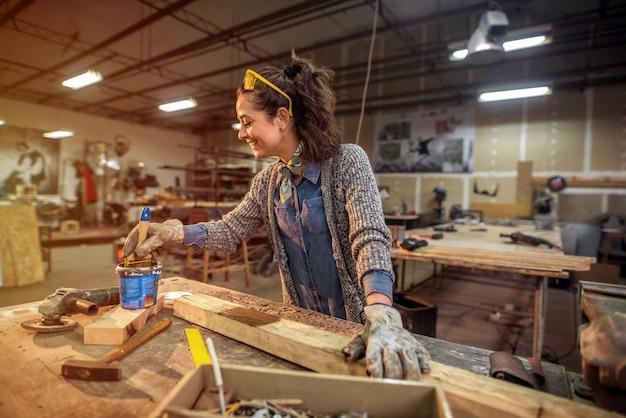 Middelbare leeftijd gelukkig timmerman schilderen wat hout in haar atelier