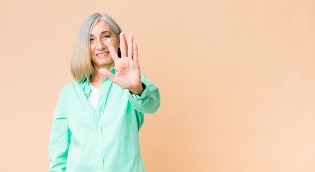Middelbare leeftijd koele vrouw glimlacht en kijkt vriendelijk, toont nummer vijf of vijfde met vooruit hand, aftellen