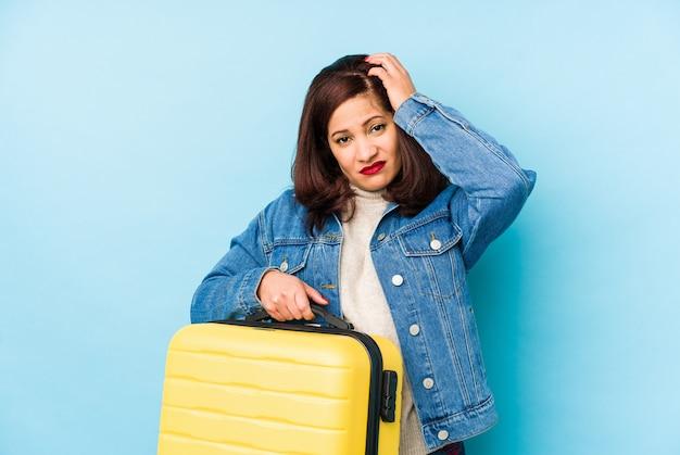 Middelbare leeftijd latijns-reiziger vrouw met een koffer geïsoleerd geschokt, ze herinnert zich een belangrijke ontmoeting.