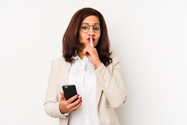 Middelbare leeftijd latijnse vrouw met een mobiele telefoon geïsoleerd houden van een geheim of vragen om stilte.