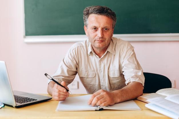 Middelbare leeftijd leraar aan de tafel zitten en kijken naar de camera.
