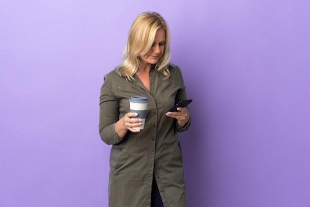 Middelbare leeftijd litouwse vrouw geïsoleerd op paarse muur met koffie om mee te nemen en een mobiel