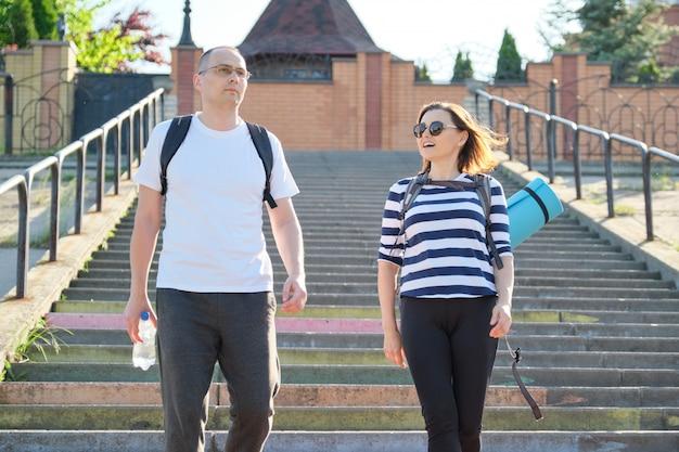 Middelbare leeftijd man en vrouw in sportkleding praten lopen
