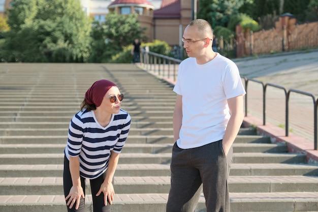 Middelbare leeftijd man en vrouw in sportkleding praten rusten na het hardlopen