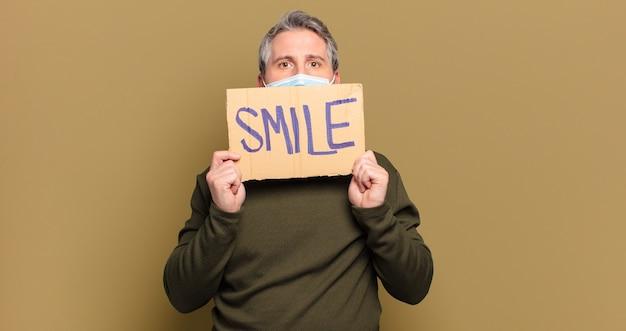 Middelbare leeftijd man glimlach concept met een beschermend masker