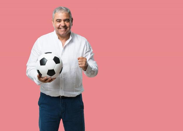 Middelbare leeftijd man glimlachend en gelukkig, met een voetbal, concurrerende houding, opgewonden om een spel te spelen