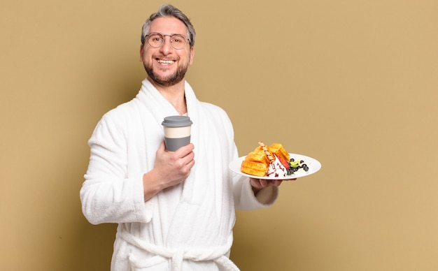 Middelbare leeftijd man met wafels om te ontbijten