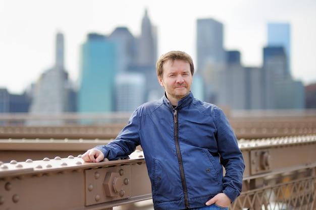 Middelbare leeftijd man op brooklyn bridge met wolkenkrabbers op achtergrond