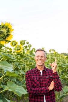 Middelbare leeftijd man wijst met zijn vinger omhoog