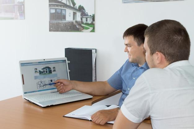 Middelbare leeftijd managers bespreken zaken terwijl ze naar hun website kijken met een laptopcomputer op het bureau.