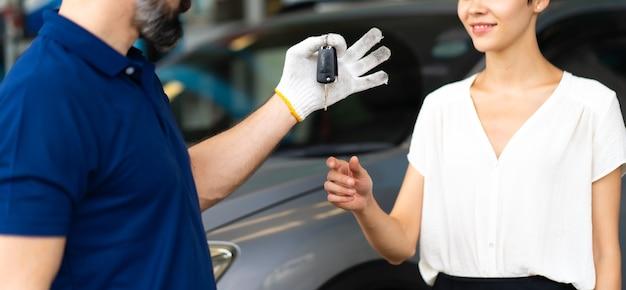 Middelbare leeftijd monteur man met baard geeft de autosleutel aan vrouwelijke klant bij auto onderhoud station en auto service garage