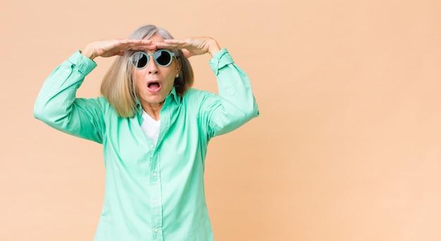 Middelbare leeftijd mooie vrouw die zonnebril draagt tegen exemplaar ruimtemuur