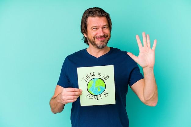 Middelbare leeftijd nederlandse man met een er is geen planeet b plakkaat geïsoleerd op blauwe achtergrond glimlachend vrolijk nummer vijf met vingers tonen.
