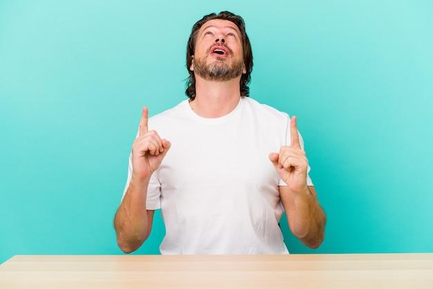 Middelbare leeftijd nederlandse man zit geïsoleerd op blauwe muur naar boven met geopende mond.