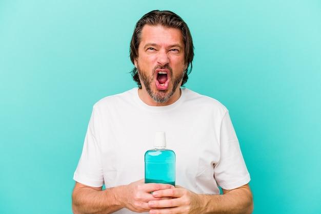 Middelbare leeftijd nederlandse man zitten met een mondwater geïsoleerd op blauwe achtergrond schreeuwen erg boos en agressief.