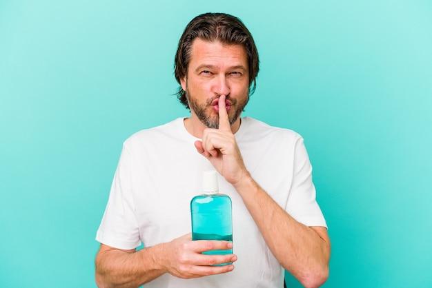 Middelbare leeftijd nederlandse man zitten met een mondwater op blauw een geheim houden of om stilte vragen.