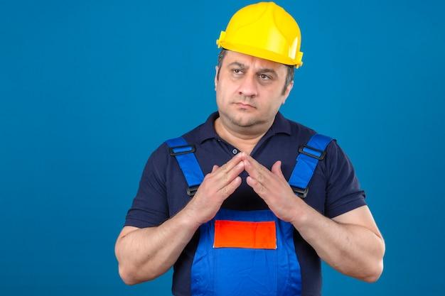 Middelbare leeftijd peinzende bouwer man met uniforme bouw en veiligheidshelm hand in hand samen en denken over geïsoleerde blauwe muur