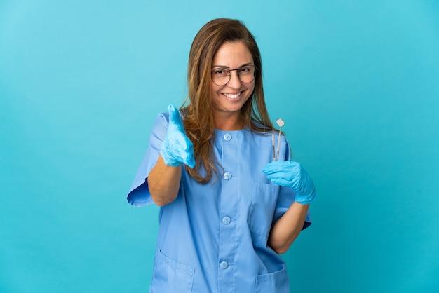 Middelbare leeftijd tandarts braziliaanse vrouw met tools over geïsoleerde handen schudden voor het sluiten van een goede deal