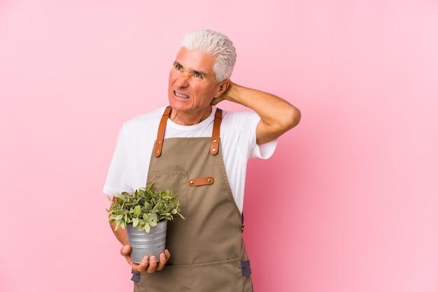 Middelbare leeftijd tuinman man geïsoleerd aanraken achterkant van het hoofd, denken en het maken van een keuze.
