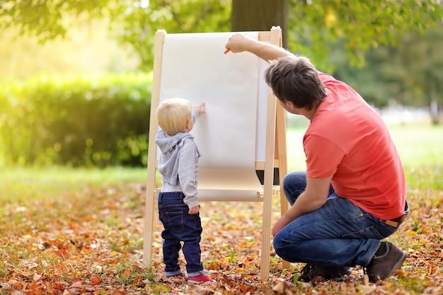 Middelbare leeftijd vader en zijn peuter zoon tekenen op witte lege papier