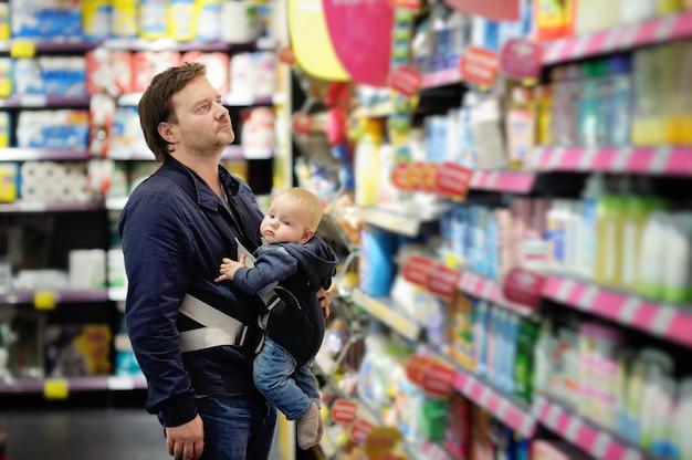 Middelbare leeftijd vader en zijn zoontje in de supermarkt