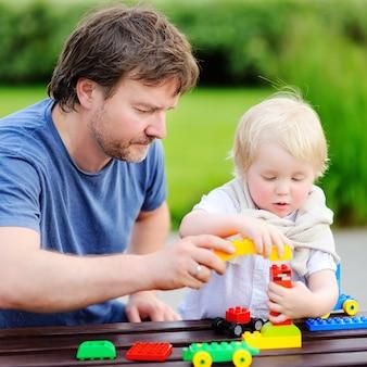 Middelbare leeftijd vader met zijn peuter zoon spelen met kleurrijke plastic blokken