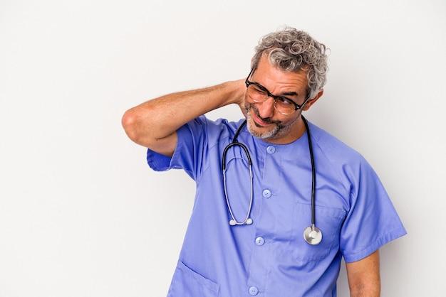 Middelbare leeftijd verpleegster blanke man geïsoleerd op een witte achtergrond achterhoofd aan te raken, denken en een keuze maken.