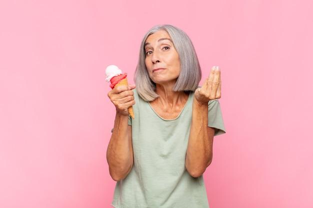 Middelbare leeftijd vrouw capice of geld gebaar maken