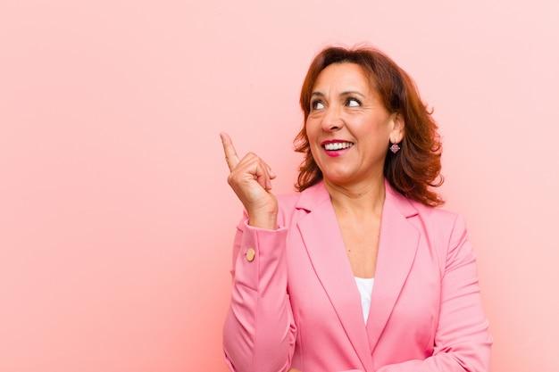Middelbare leeftijd vrouw die gelukkig glimlacht en zijwaarts kijkt, zich afvraagt, denkt of een idee roze muur heeft