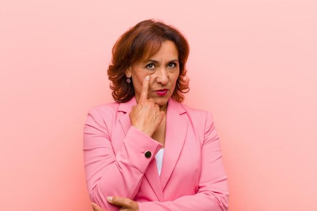 Middelbare leeftijd vrouw die je in de gaten houdt, niet vertrouwt, waakt en alert en waakzaam blijft tegen de roze muur