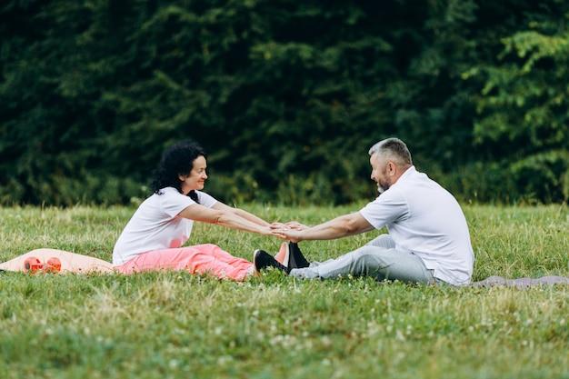 Middelbare leeftijd vrouw en man samen oefenen. sport