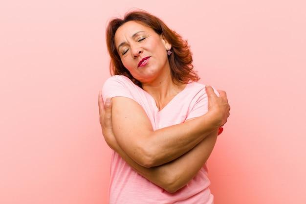 Middelbare leeftijd vrouw gevoel in liefde, glimlachen, knuffelen en knuffelen zelf