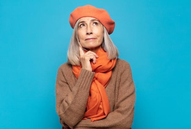 Middelbare leeftijd vrouw glimlachend gelukkig en dagdromen of twijfelende, op zoek naar de kant