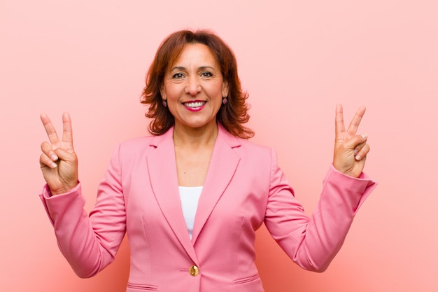 Middelbare leeftijd vrouw glimlacht en kijkt gelukkig, vriendelijk en tevreden, gebaren overwinning of vrede met beide handen