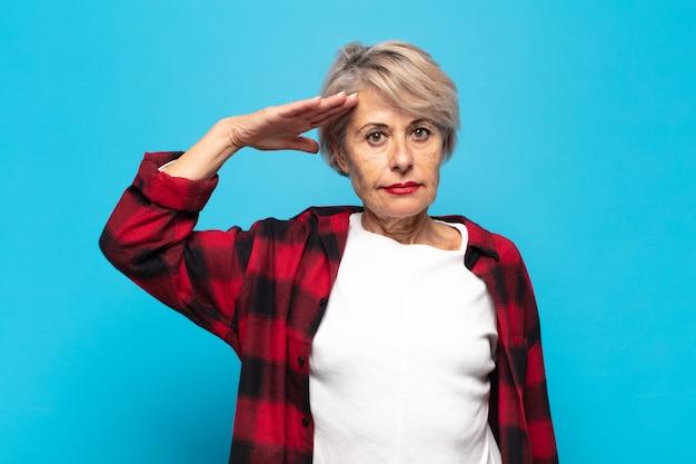 Middelbare leeftijd vrouw groet met een militaire groet in een daad van eer en patriottisme, respect tonen