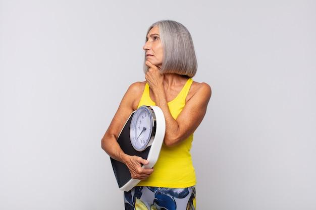 Middelbare leeftijd vrouw lachend met een gelukkige, zelfverzekerde uitdrukking met hand op de kin, benieuwd en kijkend naar de zijkant. fitness concept