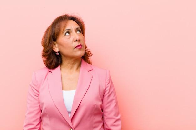 Middelbare leeftijd vrouw met een bezorgd, verward, geen idee uitdrukking, op zoek naar copyspace, twijfelende roze muur