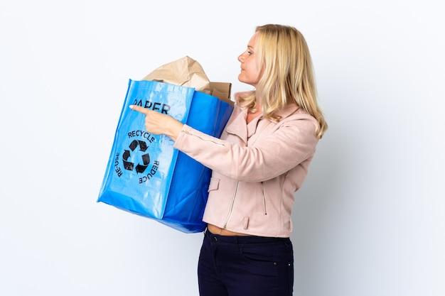 Middelbare leeftijd vrouw met een recycling zak vol papier om te recyclen geïsoleerd op een witte muur terug te wijzen